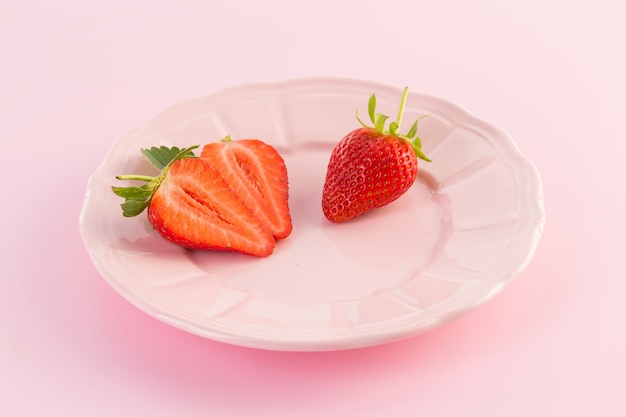Verse aardbeien op plaat op een roze achtergrond