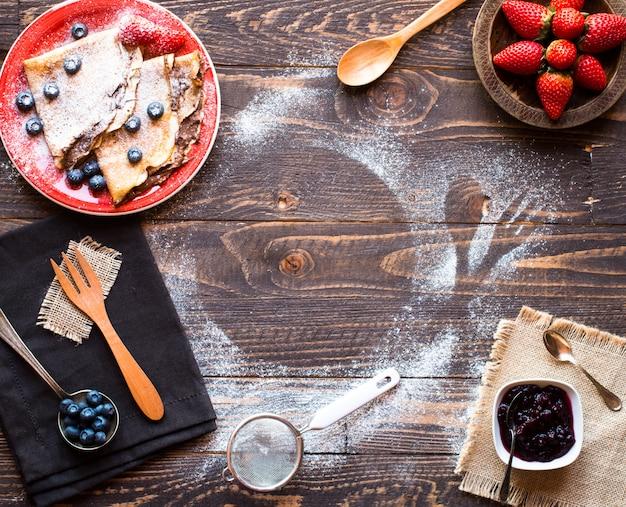 Verse aardbeien pannenkoeken of pannenkoeken met bessen en chocolade