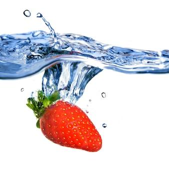 Verse aardbeien vallen in blauw water met splash geïsoleerd op wit