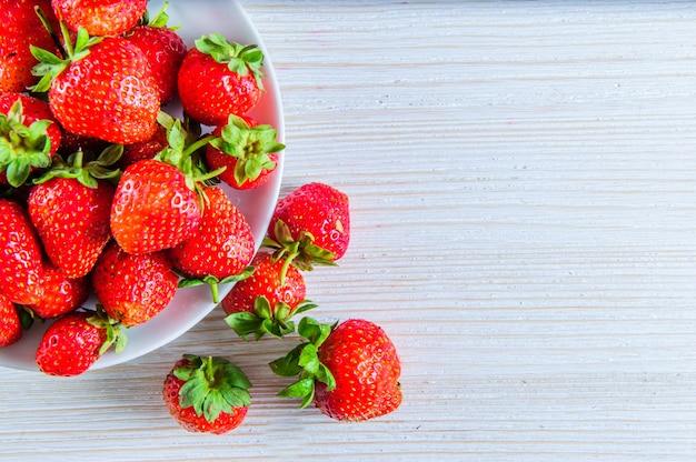 Verse aardbeienverse aardbeien op oude houten witte achtergronden