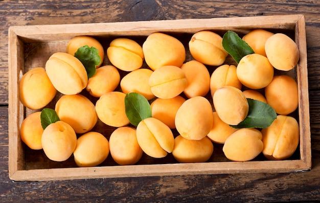 Verse abrikozen in een doos op houten tafel
