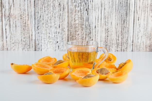 Verse abrikozen met thee zijaanzicht op witte en houten tafel