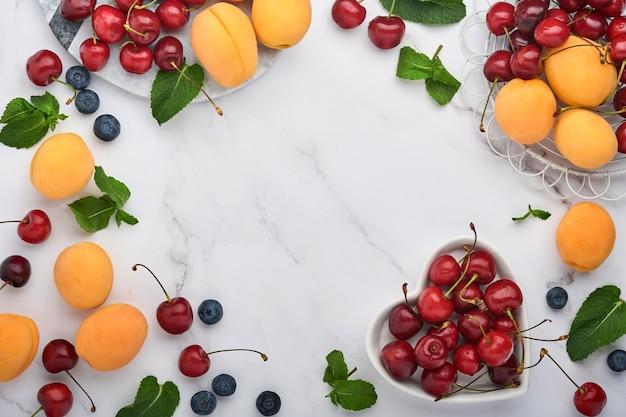 Verse abrikozen, rode kers en braambes op witte marmeren achtergrond. vegetarisch, gewichtsverlies, schoon en gezond eetconcept. bovenaanzicht. ruimte kopiëren.