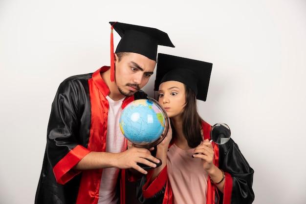 Verse afgestudeerde studenten in jurk kijken naar globe op wit.