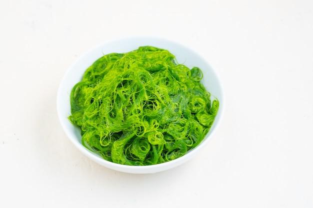 Verse algen in kom op witte achtergrond. kopieer ruimte .asia eten. natuurlijk voedsel