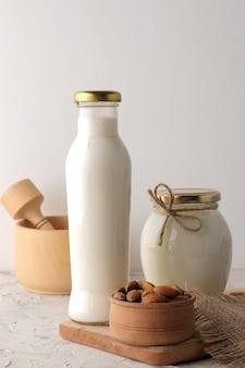 Verse amandelmelk in een glazen fles en amandelnoten op een lichte achtergrond