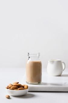 Verse amandelmelk in glazen fles en noten op grijze achtergrond