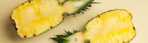 Verse ananas in twee delen gesneden en papieren frame op gele achtergrond. zomer concept. creatieve flat lag met kopieerruimte. bovenaanzicht