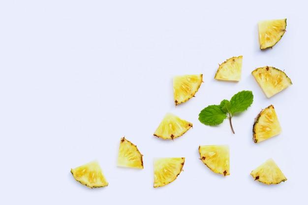 Verse ananasplakken met muntbladeren op witte achtergrond.