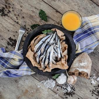 Verse ansjovis op plaat op het bakpapier met verse jus d'orange, knoflook, brood, zout en peper rond op het blauwe servet bij de vork op de houten tafel