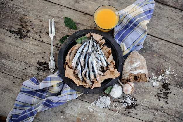 Verse ansjovis op plaat op het bakpapier met verse jus d'orange, knoflook, brood, zout en peper rond op het blauwe servet op de houten tafel