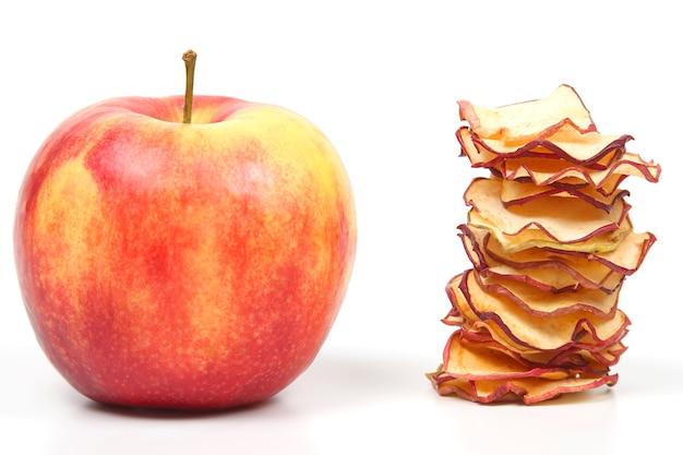 Verse appel en een stapel gedroogde appelschijfjes op witte achtergrond. vitamine fruit eten
