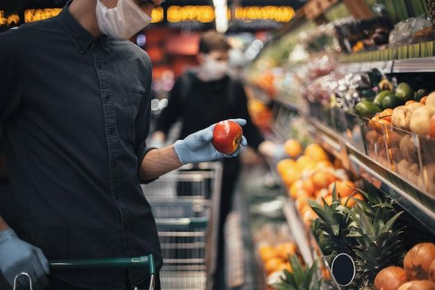 Verse appel in de handen van een man in beschermende handschoenen. hygiëne en gezondheidszorg