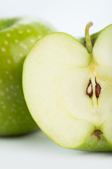 Verse appelgroene zachte rijpe halve besnoeiing die op wit bureau wordt geïsoleerd