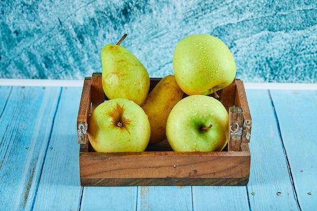Verse appels en peren in een houten doos op blauwe ondergrond.