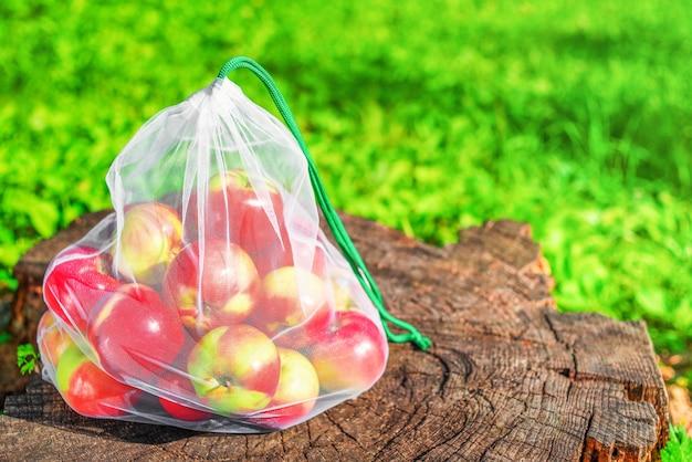 Verse appels in een herbruikbare milieuvriendelijke netzak liggen op boomstronk in de tuin. plasticvrij, zero waste, duurzame levensstijl.