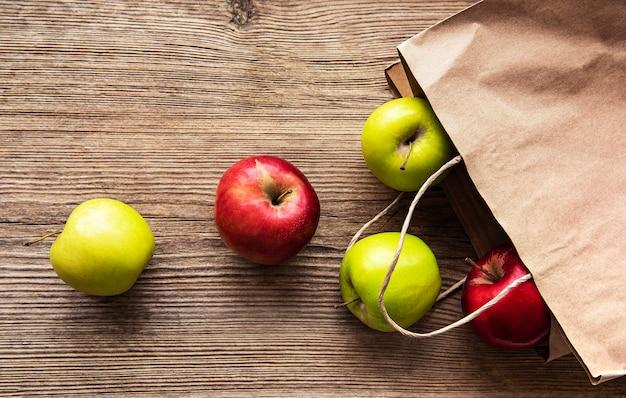 Verse appels in een papieren zak op een houten tafel