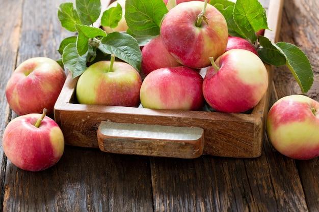 Verse appels met bladeren in een doos op houten tafel