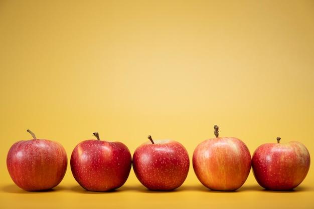 Verse appels op een felgele achtergrond in een reclame foodphoto-stijl. horizontaal
