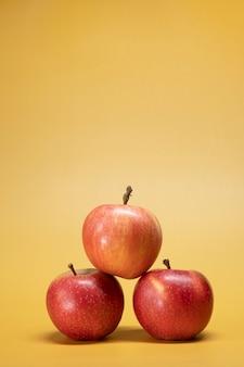 Verse appels op een felgele achtergrond in een reclame foodphoto-stijl. verticaal