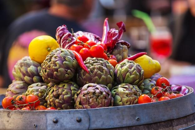 Verse artisjokken en tomaten op boerenmarkt