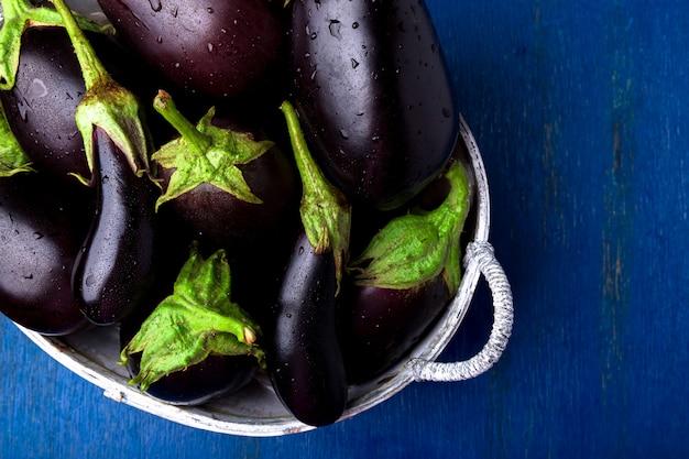 Verse aubergine grijze mand op blauwe houten lijst. bovenaanzicht copyspace. veganistische groente.