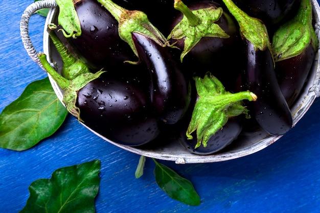 Verse aubergine in grijze mand op blauwe houten tafel.