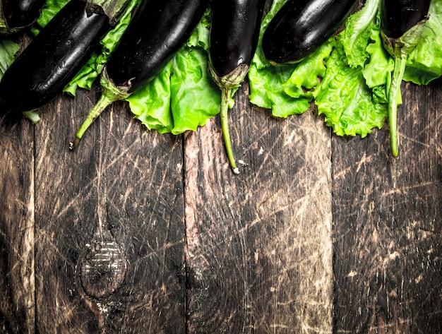 Verse aubergines op groene bladeren op een houten achtergrond