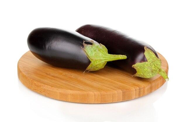 Verse aubergines op snijplank op wit