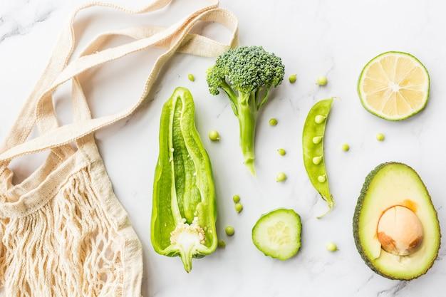 Verse avocado, limoen, broccoli, groene erwten, komkommer, groene paprika, touwzak.