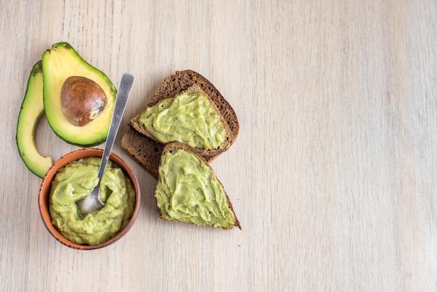Verse avocadocrème in houten kom met sneetjes brood op licht. bovenaanzicht.