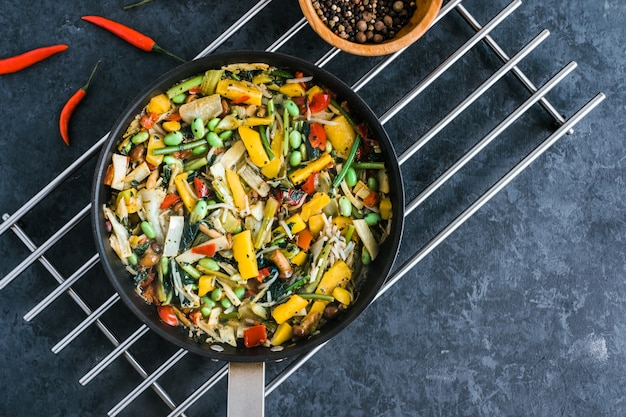 Verse aziatische groentenmix, thaise wok in een zwarte pan op de zwarte