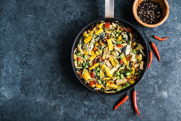 Verse aziatische groentenmix, thaise wok in een zwarte pan op het zwart