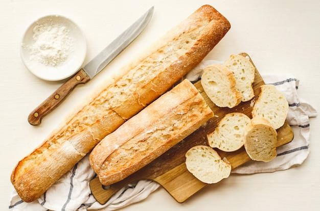 Verse baguettes met een knapperige korst gehakt op een snijplank