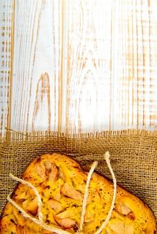 Verse bakkerij. hoogste mening van gebakken pastei met appelen op jute op witte houten. rustieke stijl.