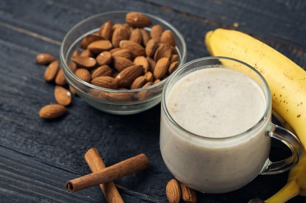 Verse banaan smoothie met amandelen op een houten achtergrond
