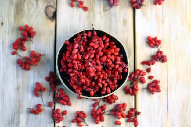 Verse berberisfamilie in een kom. rode bessen van berberisfamilie.