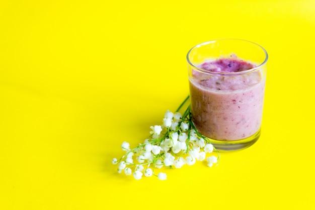 Verse bes smoothie op een geel. lelietje-van-dalen en smoothies van bessen. de lente