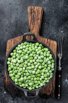 Verse bevroren groene erwten in een pan. zwarte achtergrond. bovenaanzicht.