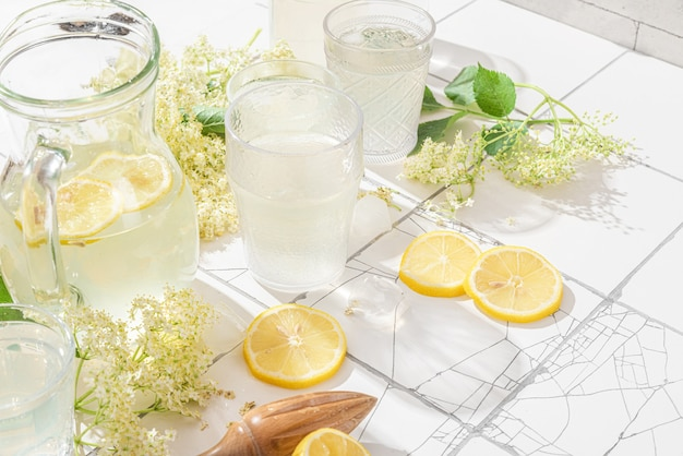 Verse bevroren mocktail of limonade met citroenen en vlierbloemen in glazen op witte tegeltafel met hard licht en schaduwen Premium Foto