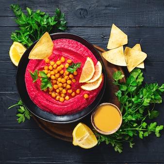 Verse bietenhummus in plaat met kikkererwten en pitabroodje bovenaanzicht gezond veganistisch voedselconcept