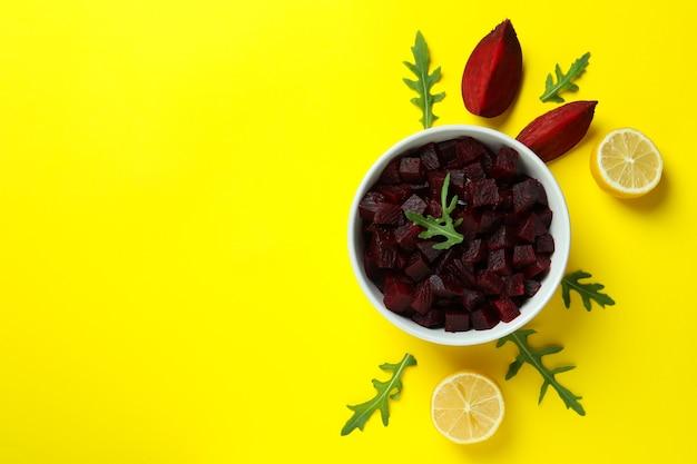 Verse bietensalade en ingrediënten op gele tafel, bovenaanzicht