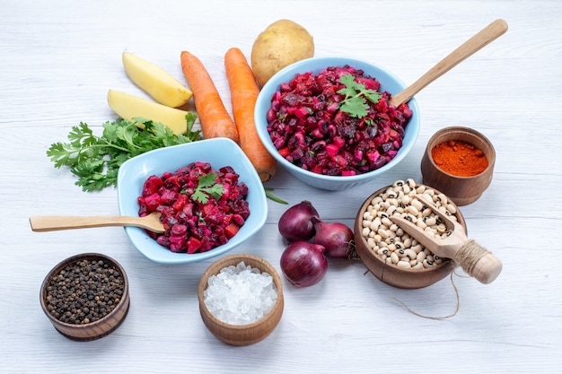 Verse bietensalade met gesneden groenten binnen blauwe platen met ingrediënten op licht bureau, groentesalade maaltijd gezondheid snack