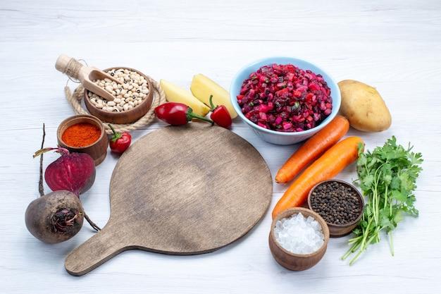 Verse bietensalade met vers gesneden groenten samen met ruwe aardappels van bonenwortelen op licht bureau