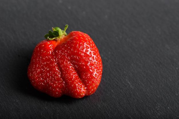 Verse biologische aardbeien geïsoleerd op een zwarte achtergrond. levering van natuurlijke producten.