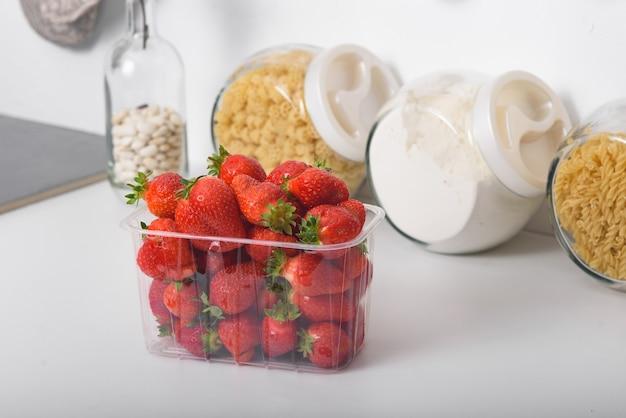 Verse biologische aardbeien in een plastic doos in de keuken. levering van biologische producten.