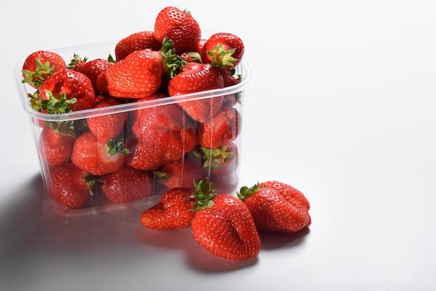 Verse biologische aardbeien in een plastic doos op een witte achtergrond. levering van biologische producten.