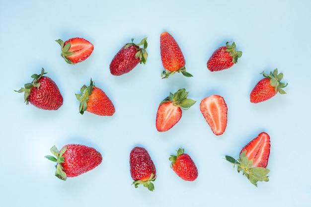 Verse biologische aardbeien op blauw. plat liggen.