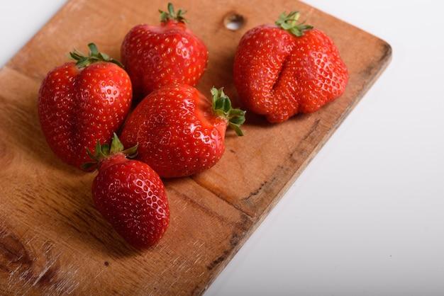 Verse biologische aardbeien op een houten bord. levering van natuurlijke producten. verpakkingen gemaakt van biologische aardbeien.