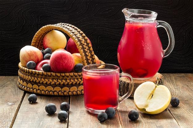 Verse biologische appels en sleedoorn in mand en heerlijke compote in kruik en mok op houten tafel